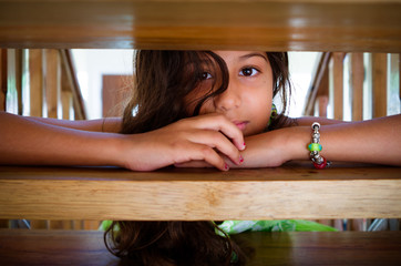 Young Girl Looking Through Stairs
