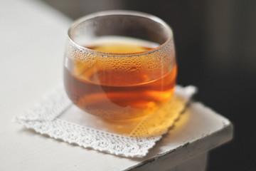 Glass of tea on square napkin on corner of table