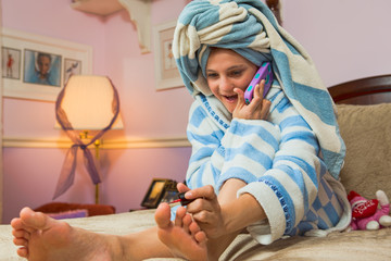 Young girl (12-13) chatting on cell phone while painting toenails