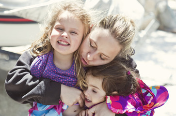 Mother embracing two daughters (4-5)