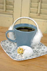 ear muffs on cup of coffee with donut
