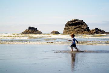 Boy ( 2-3 ) running on beach