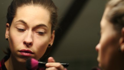 girl in front of the mirror applying makeup on her face