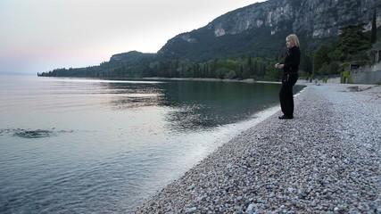 Woman throwing rocks in to sea at dawn