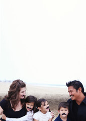 Family with three children (4-5, 6-7, 10-11) wearing mustaches on beach