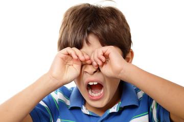 Young boy yawning on white background