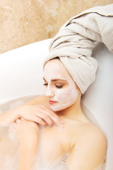 Woman relaxing in bathtub with face mask.