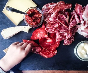 Human hand with charcuterie and cheese board