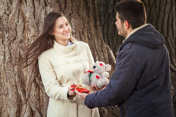Young couple exchanging presents for Valentine's Day in nature