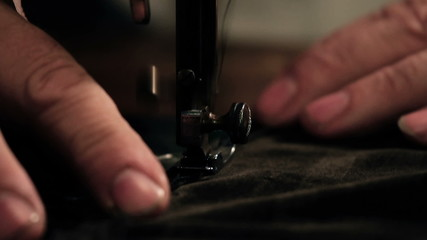 Close up shot of a tailors hands sewing a dress