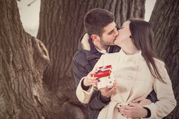 Romantic young couple kissing and holding gift