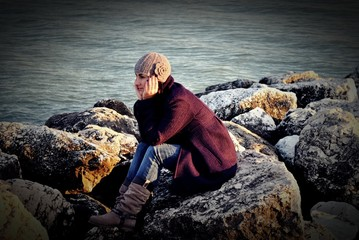 Young woman sitting on rocks by sea