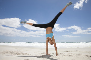 Young woman doing handstand on beach