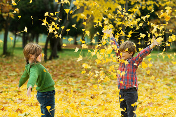 Boy (6-7) and girl (6-7) throwing autumn leaves in park