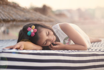 Charming little girl (6-7) in summer dress dreaming and smiling at beach