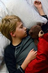 Boy (12-13) Sleeping with teddy bear