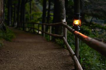 Illuminated oil lamp on fence along woodland path