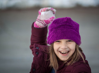 Portrait of girl (6-7) holding snowball laughing