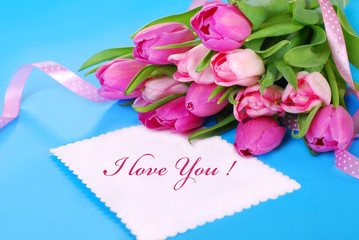 bunch of pink tulips and white card with love text