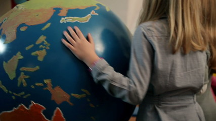 Young kids playing with huge Earth globe