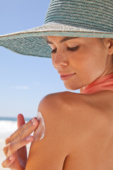 Close up of young woman on the beach applying sun cream