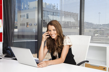 Businesswoman in office using phone and laptop