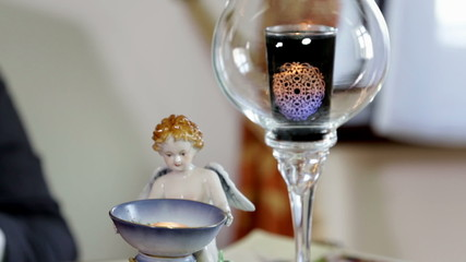 Detail of little statue and a candle in a glass