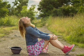 Blonde girl (14-15) sitting on dirt road and laughing