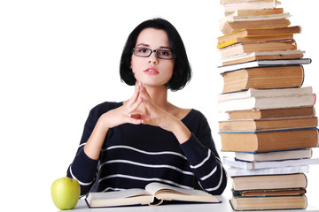 Concentrated woman sitting with stack of books