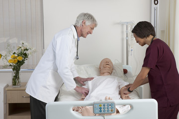 Doctor with nurse examining cpr dummy