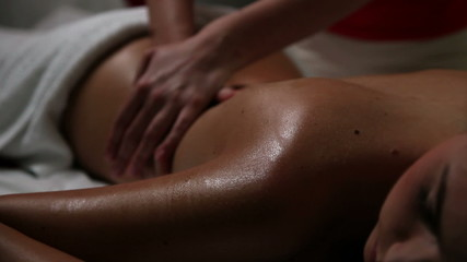 Young woman having a sensual back massage in a beauty spa center