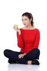 Woman sitting cross-legged holding an apple