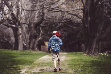Boy (8-9) walking down dirt track