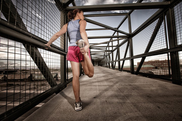 USA, Colorado, Woman runner stretching on bridge