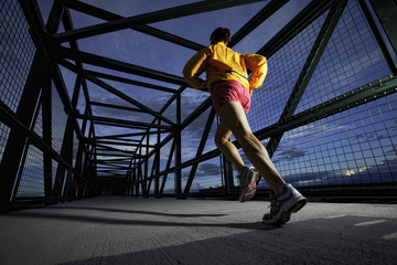 USA, Colorado, Woman jogging across bridge at dusk