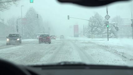 It is snowing while driver comes close to the crossroads