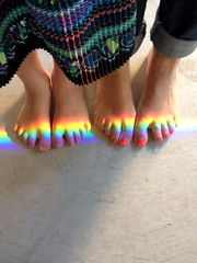 Mother and daughter feet with beam of rainbow light shining across toes