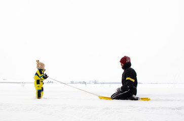 Son pulling father on sledge (2-3 years)
