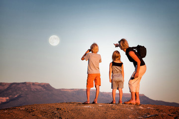 Mother and her children (5-6) looking at moon