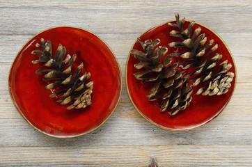 three pine cones on a red ceramic bowl