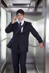 Businessman in lift on the phone