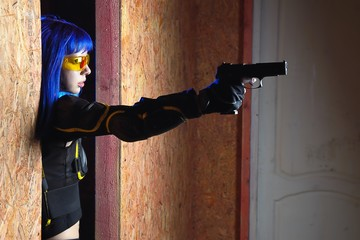 Beautiful girl with blue hair holding gun in strikeball location