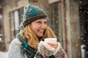 Woman holding cup of tea and enjoying snow