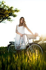 Young adult women standing with bicycle