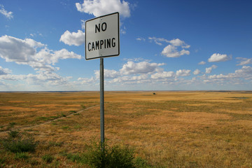 No camping sign in middle of meadow