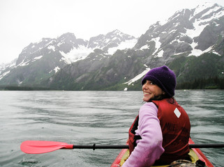 USA, Alaska, Young woman kayaking near glaciers in Kenai Fjords National park