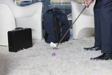 Businessman practicing golf on rug in office