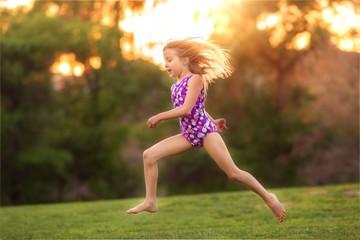 USA, Little girl (8-9) wearing swimsuit jumping in back yard