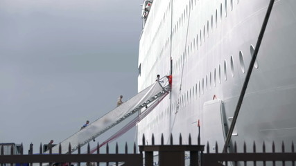 Shot of people ascending the stairs to board on white cruiser made behind fence