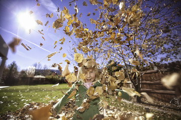 Girl in garden in swirl of autumnal leaves, portrait